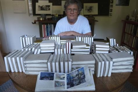 Artist Charles Ritchie photographed with the 151 sketchbook/journals he has completed since 1977