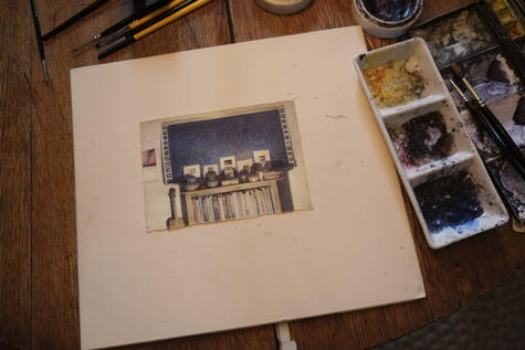 The image shows the drawing mounted to board resting on the drawing table beside watercolors, brushes, and porcelain mixing palette with gum arabic.