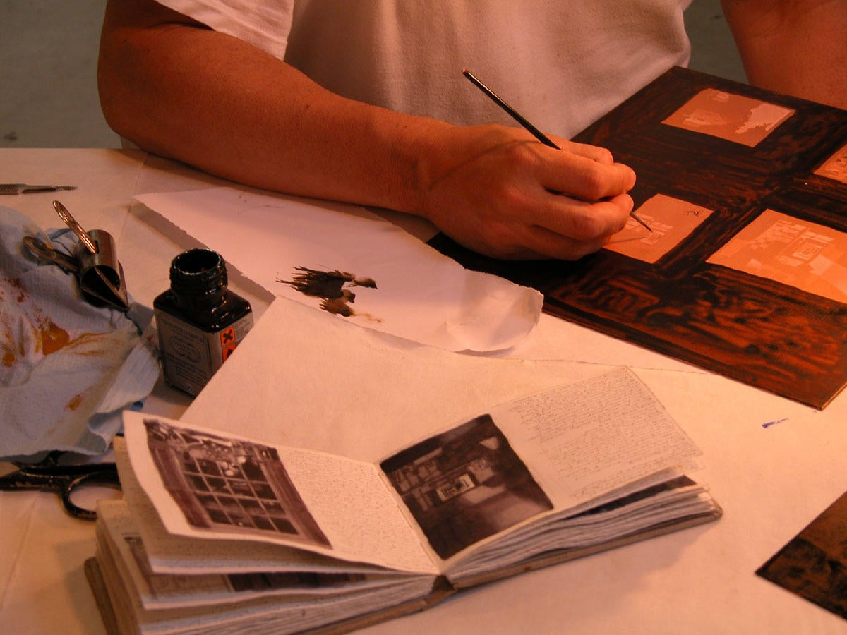 Photograph of the artist working on an aquatint plate image